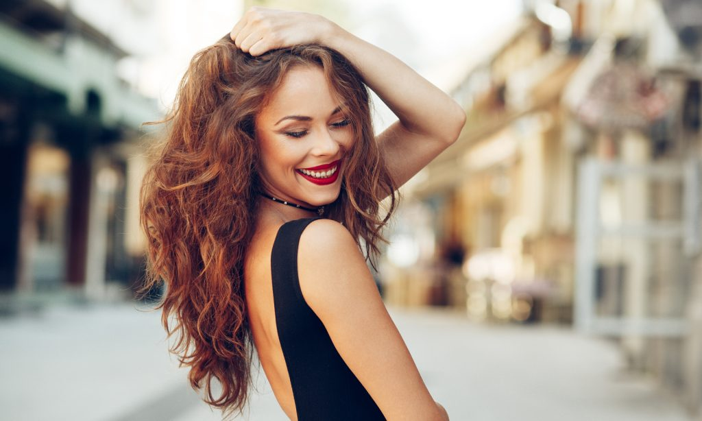 AdobeStock woman smiling smile happy holding curly hair, Six Secrets to Aging Well You Need to Know