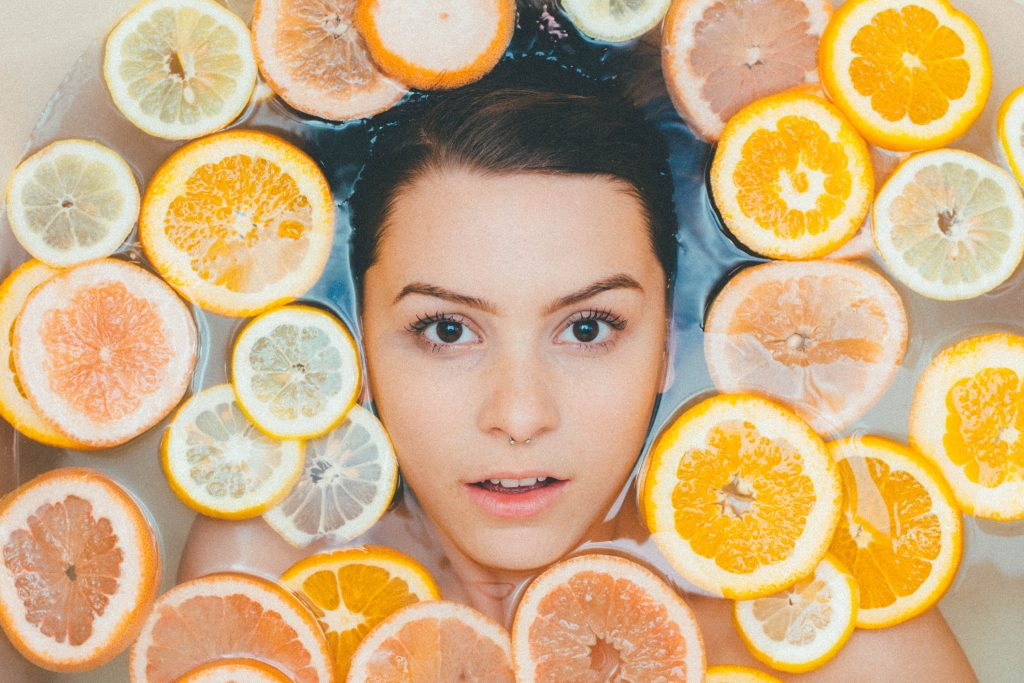 face of a beautiful young lady at the center of different kinds of citrus fruits, uses of lemon, 7 Ways to Use Lemons for Health and Beauty