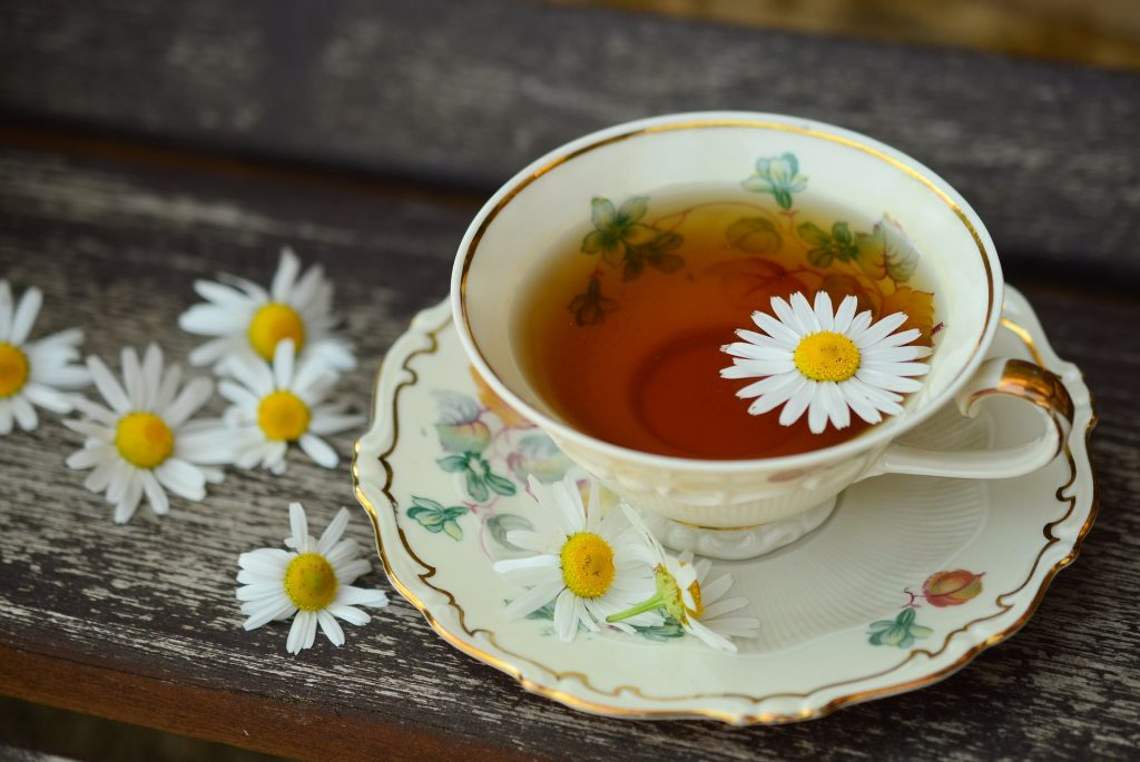 one porcelain cup with chamomile tea on top of gray wood with seven white flowers scattered beside the cup, health benefits of chamomile tea, Reasons to Sip Chamomile Tea Every Day