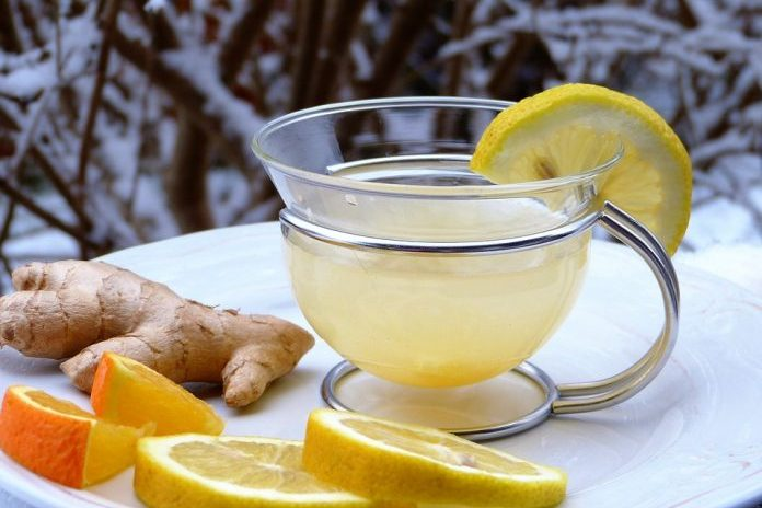 one ginger root and 4 slices of lemon beside a transparent cup of ginger tea with a lemon garnish on top of white counter background winter branches with snow, natural remedies for a sore throat, Ease Your Sore Throat with These Remedies