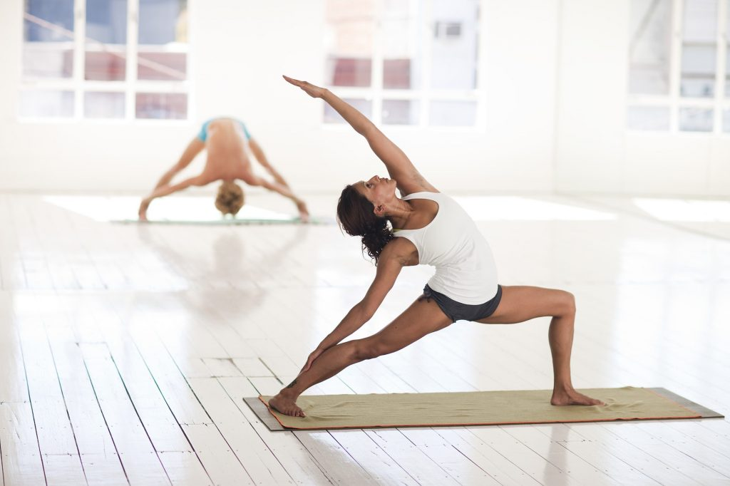 fit woman wearing white top and black shorts doing a yoga pose in front of a woman, background studio with white walls, exercises for stronger bones, Exercises that Promote Stronger Bones