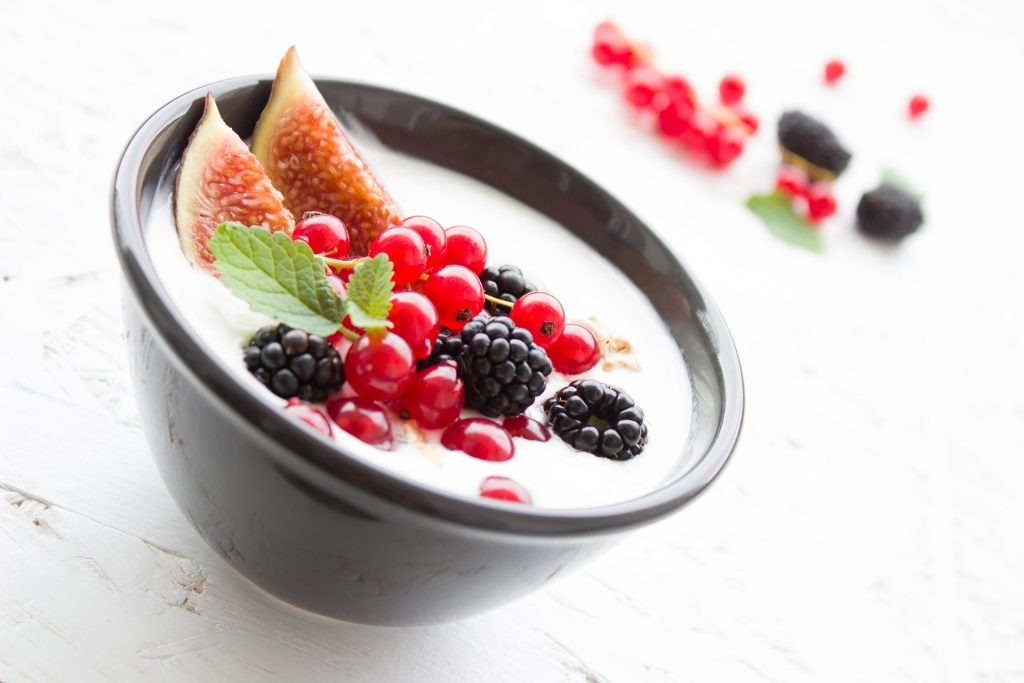 one black bowl of vegan yogurt with two slices of figs, blackberries, and cherries, white background, plant sources of calcium, Dairy-Free Products Rich in Calcium